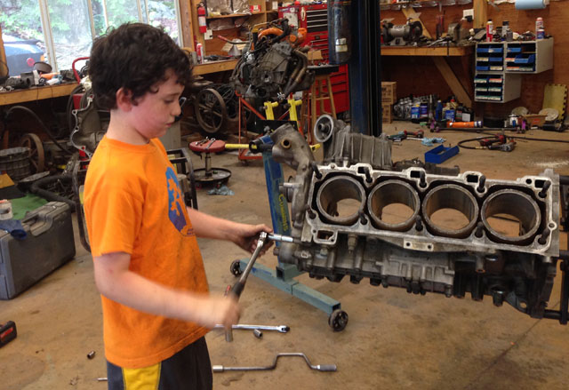 Young Hack Racer taking apart an engine